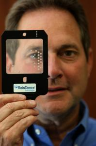 Christopher D. McNary, president of RainDance Technologies, with a fluidic circuit chip used in the DNA sequence enrichment process.