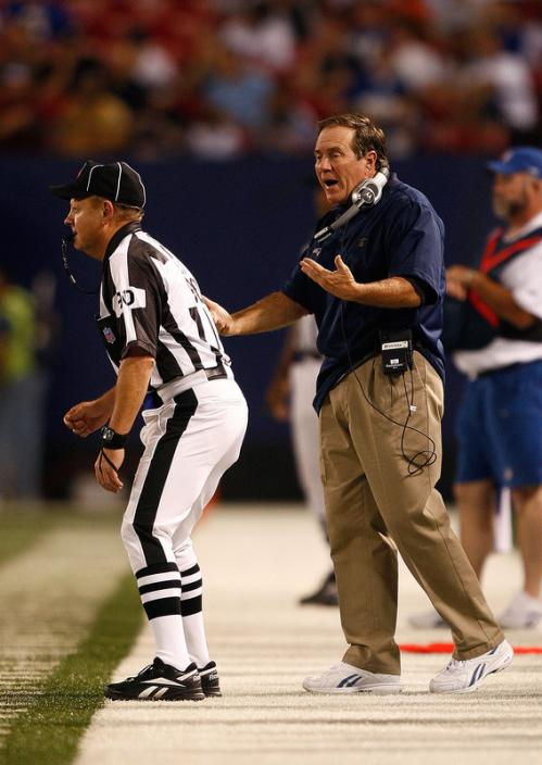 New England Patriots head coach Bill Belichick (right) complains to an official.