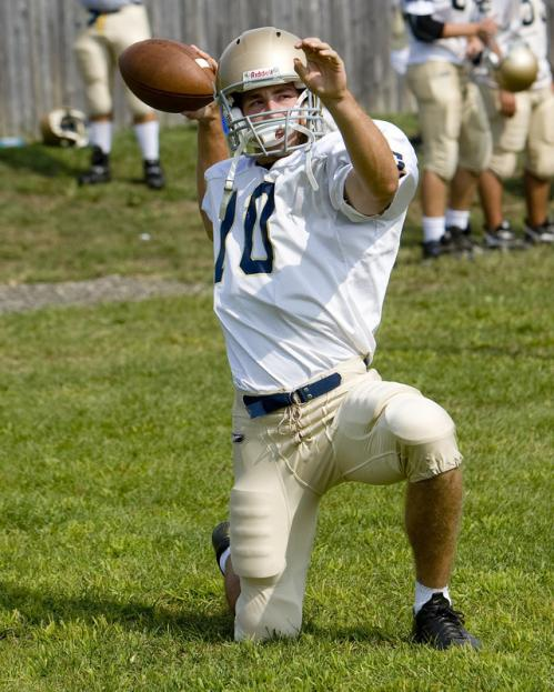 Coyle & Cassidy quarterback Conor Henry warms up before practice by throwing from one knee.