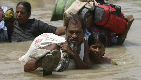 People displaced by flooding carried their belongings as they waited to be rescued yesterday in Chondipur village in India's Bihar state. About 700,000 people are trapped in remote areas.