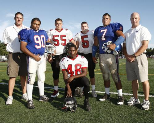 Quincy High School football captains E.J. Louis (90) and Sean Gray (7) pose with North Quincy High School football captains RJ Bardon (55), Terrell Staley (48) and Patrick Watkins (5) and the respective coaches Jim Connor of North Quincy, left, and Bill Reardon of Quincy, right, at the Patriot League Jamboree.