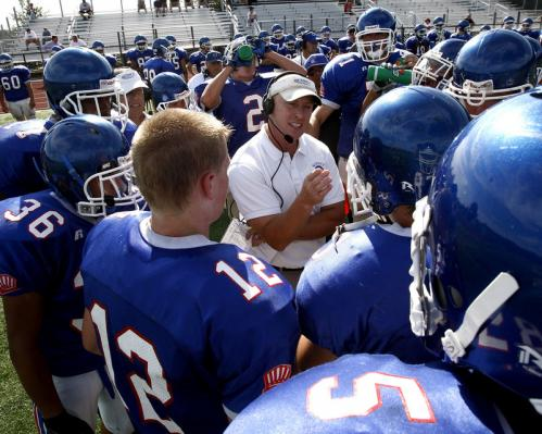 Quincy High School head football coach Bill Reardon, center, talks to his team during a timeout at the Patriot League Jamboree.