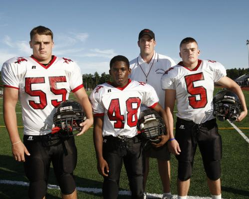 North Quincy High School football captains RJ Bardon (55), Terrell Staley (48) and Patrick Watkins (5) pose with head coach Jim Connor.