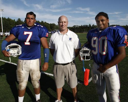 Quincy High School football captains Sean Gray (7) and E.J. Louis (90) pose with their coach Bill Reardon.