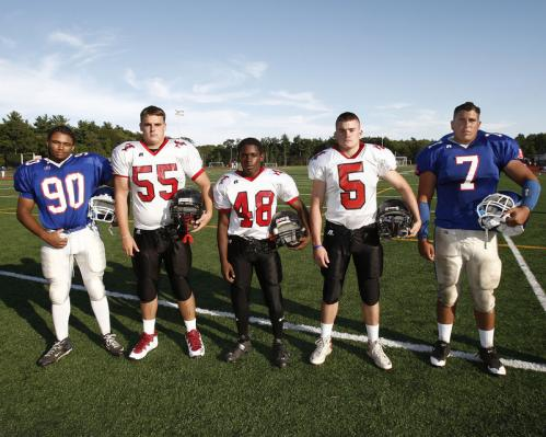 Quincy High School football captains E.J. Louis (90) and Sean Gray (7) flank the North Quincy High School football captains RJ Bardon (55), Terrell Staley (48) and Patrick Watkins (5) at the Patriot League Jamboree at Whitman-Hanson High. Both teams will be in the Patriot League this coming season.