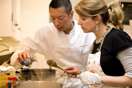 Dana Volman watches as chef and teacher German Lam spices a basic tomato sauce.