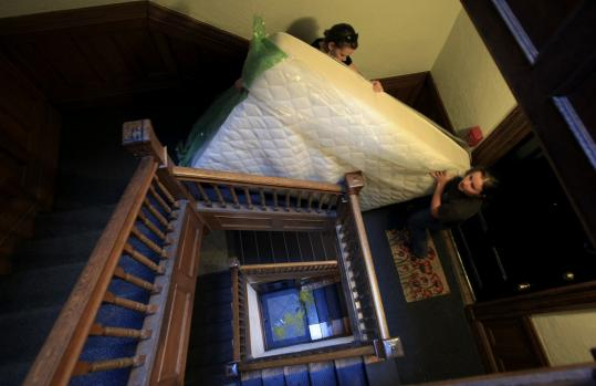 Boston College students Jeanette Hall (above, left) and Jenna Bee moved a mattress from a Beacon Street apartment to a place closer to campus.