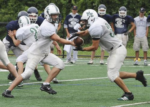 Manchester-Essex quarterback Pat Orlando, left, hands the ball off to Ben Kekeisen during a scrimmage against Pingree.