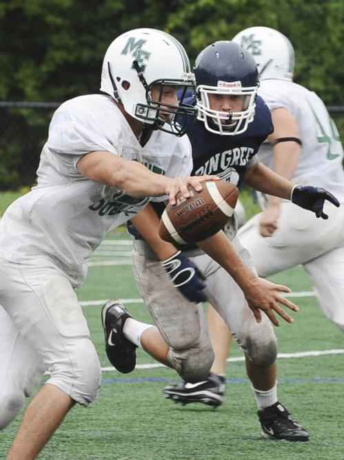 Manchester quarterback Pat Orlando, left, fakes a handoff as Pingree's Campbell Rawlins rumbles towards him during a scrimmage.