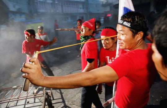 A pro-government supporter uses a sling against anti-government protesters yesterday in Bangkok, Thailand.