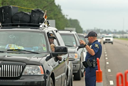 Louisiana State Trooper Mike Nicolini told a driver yesterday that he could not continue to New Orleans at a checkpoint at the Slidell/New Orleans Causeway. Those with certain placard designations were allowed into the city while others were redirected.