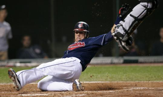 The Indians' Asdrubal Cabrera scores in the fourth, sliding under White Sox catcher A.J. Pierzynski, who leaves the scene to collect a high throw.