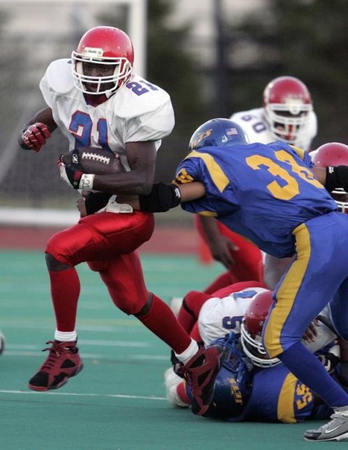 Charlestown's Travis White (21) breaks away from East Boston's Valter Gomes (38) during a football game last September.