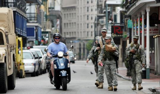 A man rode his scooter on Bourbon Street past US Army National Guard soldiers yesterday in New Orleans. Officials announced that residents would be allowed to return to their homes today, two days after Hurricane Gustav spared New Orleans a direct hit.