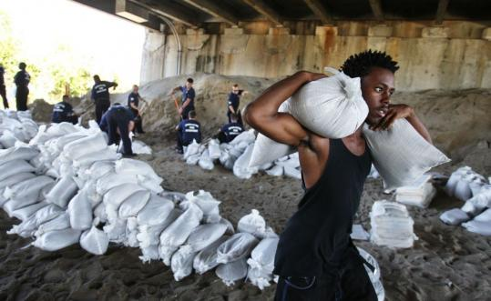 Cortez Simmons carried sand bags as he prepared for the possible landfall of Tropical Storm Hanna in Charleston, S.C., as firefighters filled sand bags under Interstate 526 yesterday.