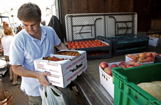 Christopher Crandall picks up produce at a farmers' market in Somerville for his delivery business In Season.