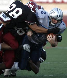 Dracut quarterback Matt Grimard (3) carries two Brockton defenders with him during first-half action.