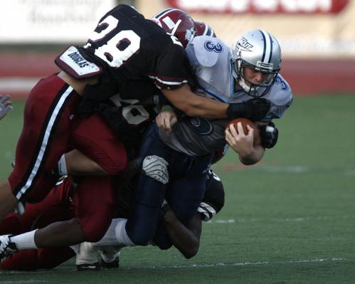 Dracut quarterback Matt Grimard (3) carries two Brockton defenders with him including linebacker Alex White (28).
