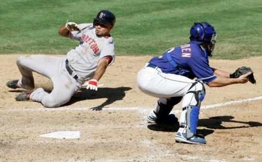 Coco Crisp slides around Texas catcher Taylor Teagarden to score a sixth-inning run. Crisp had two hits and two runs.