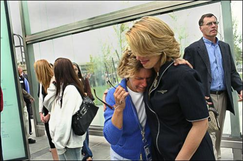 While walking through the memorial, United Airlines flight attendants Sherill Moulton, left, and Sara Nelson comfort each other.