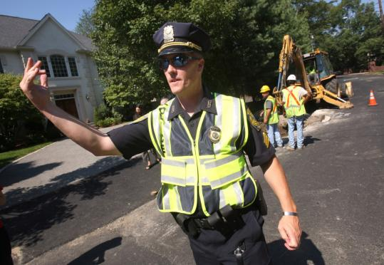 Sergeant Glenn Chisholm directs traffic at a Dudley Road project in Newton, where the total tab for police details topped $2 million last fiscal year.