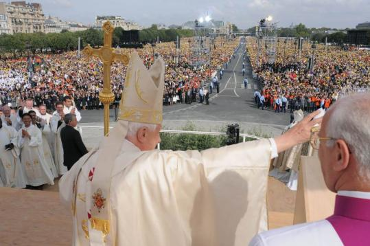 Pope Benedict XVI waved during an outdoor Mass yesterday at the Esplanade des Invalides in Paris. After the Mass, he traveled to Lourdes to drink from a spring famed for its cures.