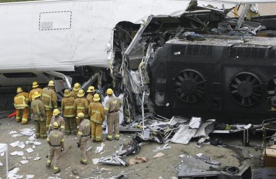 Los Angeles firefighters yesterday surveyed the wreckage of a commuter train that collided head-on with a freight train in the Chatsworth section of Los Angeles on Friday.