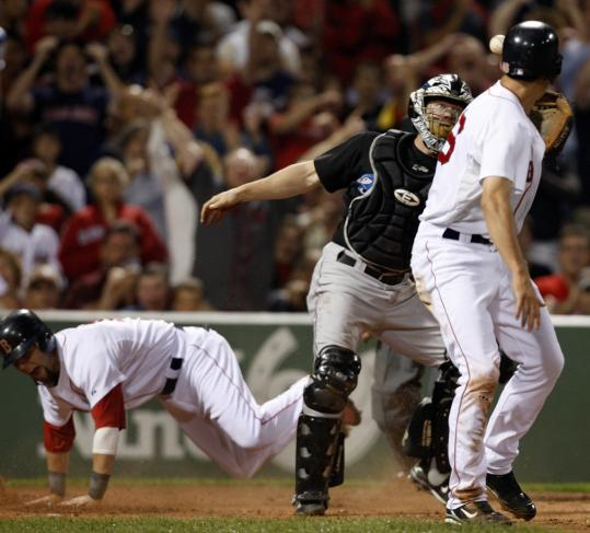 Dustin Pedroia took the low road to score on a wild pitch in the first inning of Game 2, then dusted himself off and collected his 200th hit of the season later in the game.