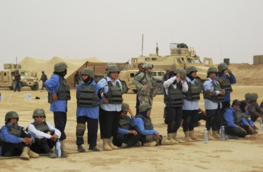 Iraqi female police recruits await target practice last week at a police academy in Udaim, north of Baghdad.