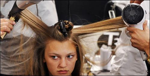 A model has her hair styled backstage before the spring 2009 collection of Carolina Herrera is presented during Fashion Week in New York, Monday Sept. 8, 2008.