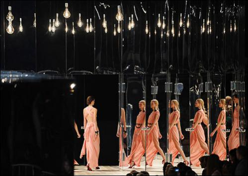 Models present outfits as they are reflected in mirrored doors at the Marc Jacobs spring 2009 collection at Mercedes-Benz Fashion Week on September 8, 2008 in New York.