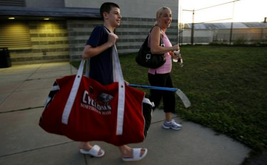 Dawn Tiorano, with son R. J. in Everett last week, said hockey parents can get intense, often a result of the long hours and big money they invest.