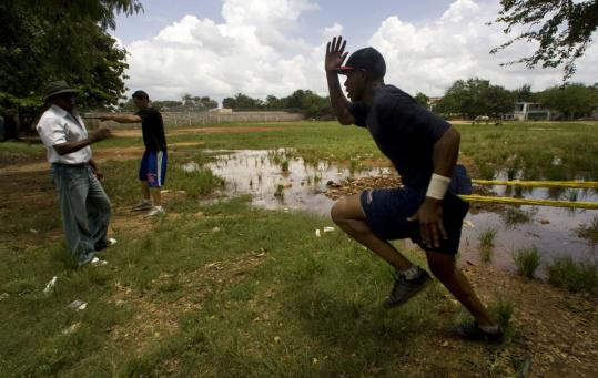 A flooded field in a Los Mina neighborhood in Santo Domingo didn't stop players from their daily training routine.