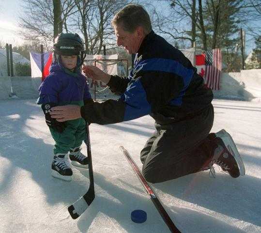 Jack Falla, helping a neighborhood boy tighten his helmet, annually fashioned an ice rink out of his yard for his family and friends in Natick.