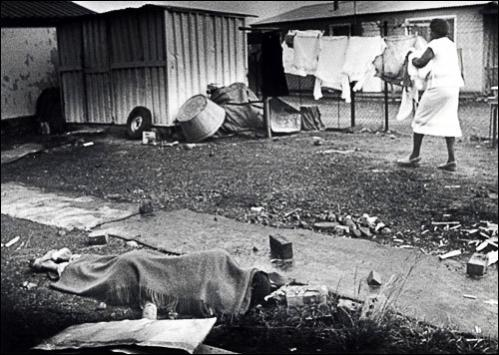 A woman picks laundry off the line in Leandra in 1986 while the body of a person just hacked to death during funeral services for Chief Ampie Mayisa lies a few feet away. Mayisa was slain by township vigilantes and this was believed to be a retailitory slaying against a vigilante.