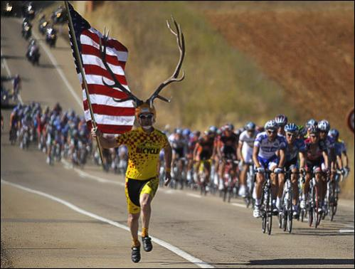 A spectator holding a U.S. flag and wearing antlers runs with the pack of riders during Stage 16 of the Tour of Spain between Ponferrada and Zamora September 16, 2008.