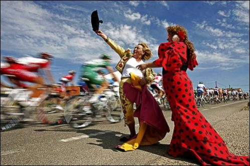 Two women, one dressed as a bullfighter, left, and the other as a flamenco dancer, cheer the pack of riders during the 17th stage of the Spanish Vuelta cycling race to Valladolid, Spain, Wednesday, Sept. 17, 2008.