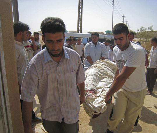 Men carried the body yesterday of a person killed in an overnight raid in the town of Adwar, near Samarra, Iraq.