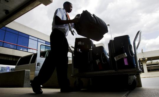 Baggage handler Mikaaill Heard loads luggage onto a cart outside the American Airlines terminal at Philadelphia International Airport in Philadelphia. American reports award tickets are up 10 to 15 percent, providing an economic boost to the airline.