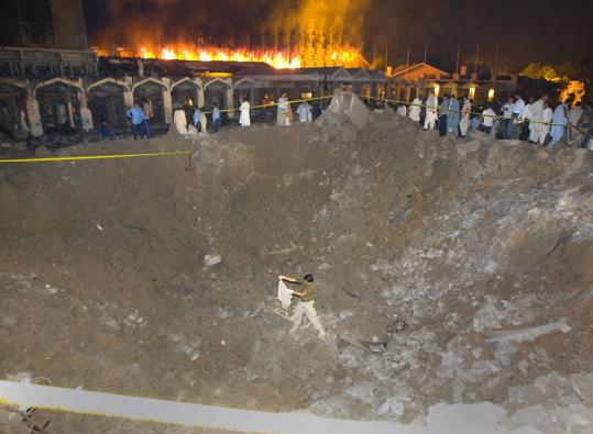 Security officials collected evidence yesterday from the 30-foot crater left by the suicide truck bombing in Islamabad, Pakistan. In the background, a fire raged at the Marriott Hotel.