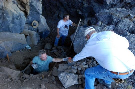 University of Oregon archaeologist Dennis Jenkins (center) handed up a device to a co-worker for measuring temperature at the Paisley Caves outside Paisley, Ore.