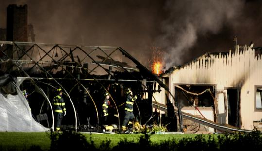 Justine Hunt/Globe StaffFirefighters put out a blaze at the 3,000-square-foot produce stand at Verrill Farm on Wheeler Road in Concord yesterday.