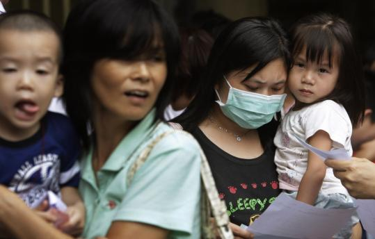 Children and parents waited for health checkups at a clinic in Hong Kong yesterday amid widespread concerns about contaminated Chinese milk.