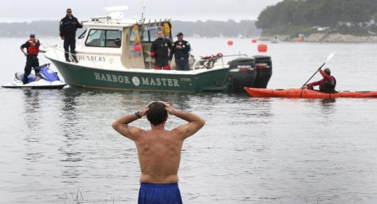Heart recipient George Senerchia waded into water yesterday to hear teammate Peter Kenyon, 70, didn't finish swim.