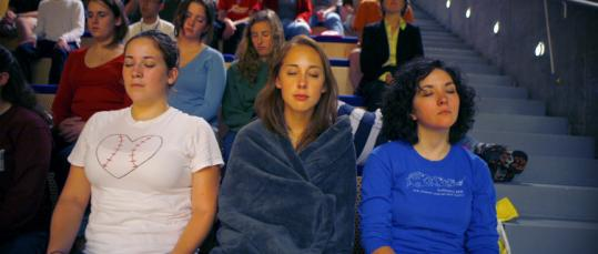 Tracey Hayse (center) came to a sleep class at MIT wrapped in a blanket Friday. She and classmates do relaxation exercises.