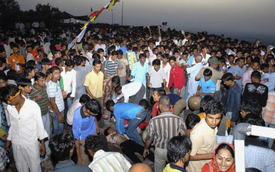 Onlookers gathered yesterday after a stampede at the Chamunda Devi temple inside the 15th century Mehrangarh fort in Jodhpur, India. ''Someone slipped,'' Home Minister G.C. Kataria said. ''Then people just kept falling over one another.''