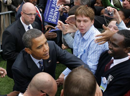 Barack Obama greeted voters yesterday after a rally in East Lansing, Mich. At another stop in the state Obama offered government aid to help the auto industry retool its factories.
