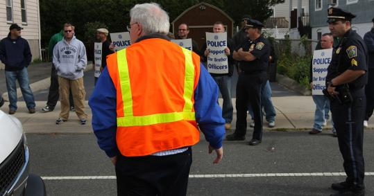 Mike Hornbrook, chief operating officer of the Massachusetts Water Resources Authority, faced demonstrators in Everett yesterday, one of two sites later abandoned by his work crew.