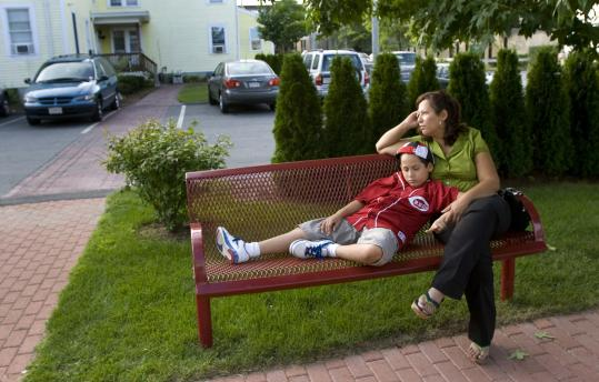 Jonathan Santiago, 9, rested with his mother, Frances, outside the House of Hope homeless shelter, where they live, in Lowell.