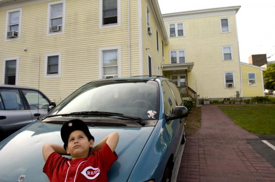 Jonathan Santiago daydreams outside the House of Hope homeless shelter in Lowell, where he lives with his mother, Frances.